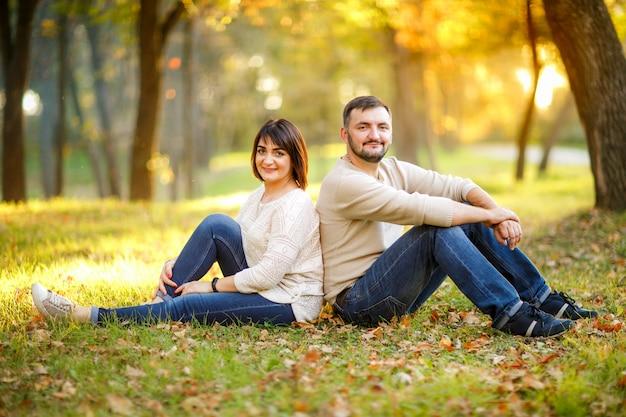 Pareja de enamorados se sienta en las hojas caídas en el parque
