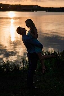 Pareja de enamorados silueta de luz trasera en el lago naranja atardecer, romántico.