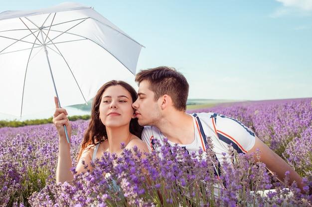 Pareja de enamorados bajo una sombrilla blanca en un campo de lavanda