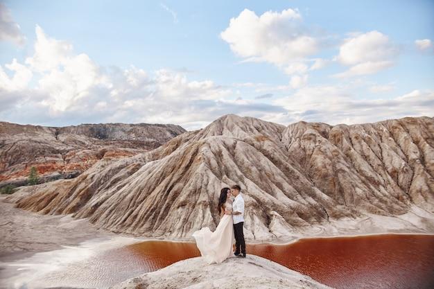Pareja se encuentra en el precipicio de la montaña y el lago rojo y abrazándose
