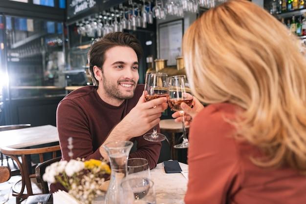 Pareja enérgica entusiasta bebiendo vino y colgando