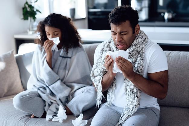 Pareja de enfermedades con la temperatura sentado en el sofá