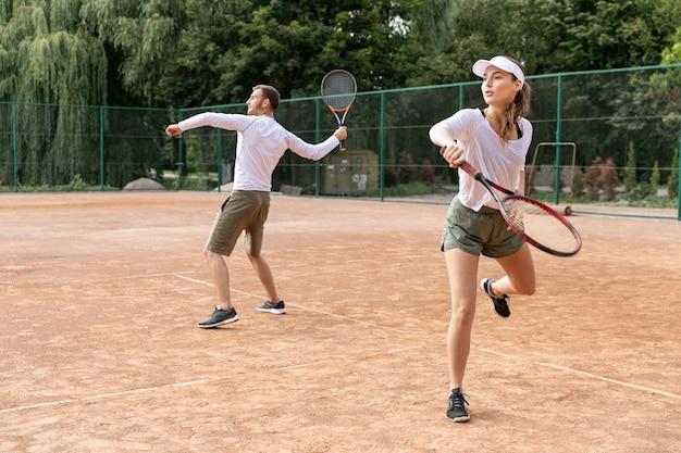 Pareja enfocada jugando tenis