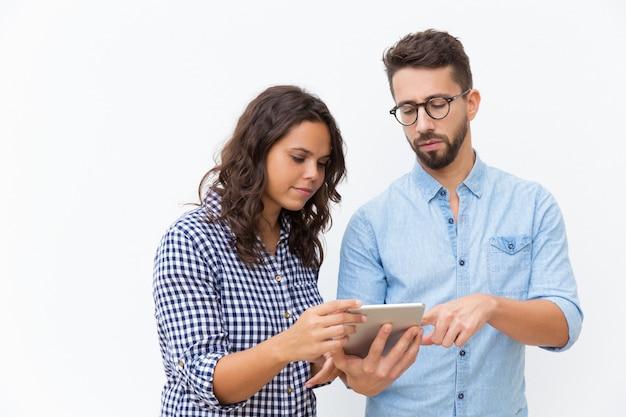 Pareja enfocada con tableta analizando presupuesto familiar