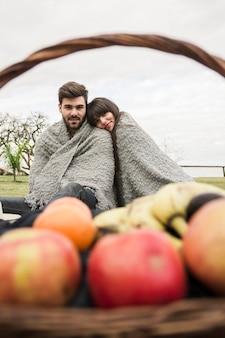Pareja envuelta en una manta sentada frente a una cesta de frutas