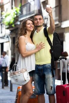 Pareja con equipaje haciendo selfie