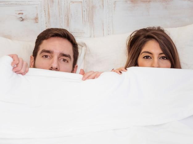 Pareja escondida bajo una manta blanca en la cama
