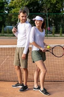 Pareja espalda con espalda en la cancha de tenis