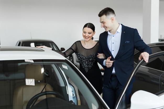 Una pareja de esposos elige un automóvil para comprar en un concesionario de automóviles
