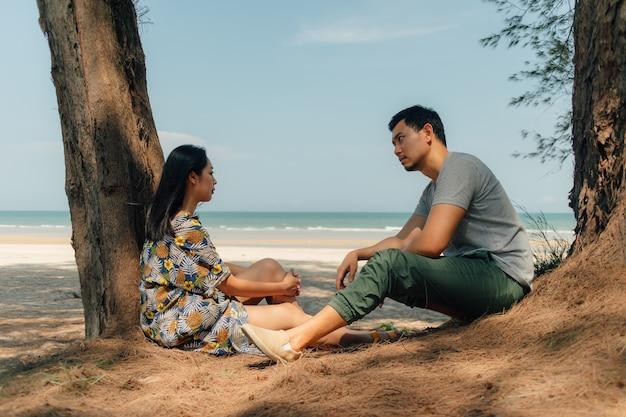 Pareja están sentados juntos en la playa bajo el árbol de pino.