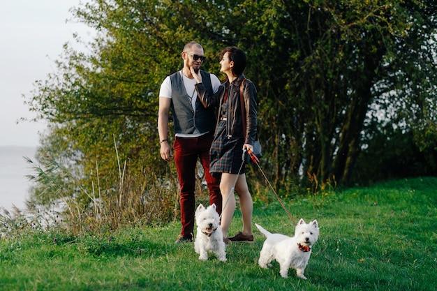 Una pareja con estilo pasea por el parque con dos perros blancos.