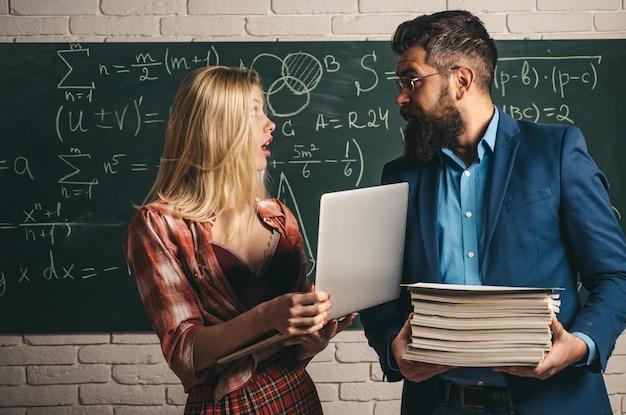 Pareja de estudiante bastante sexy sosteniendo un montón de libros y profesor guapo con barba o