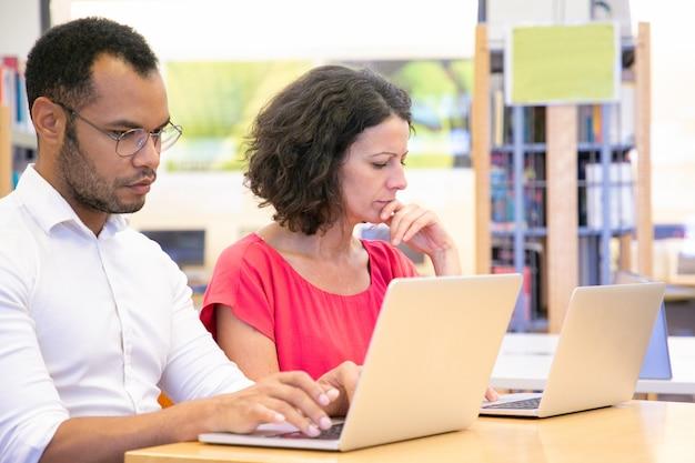 Pareja de estudiantes adultos serios trabajando en proyecto en biblioteca