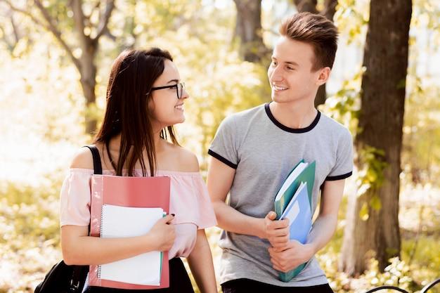Pareja de estudiantes hablando al aire libre en un parque