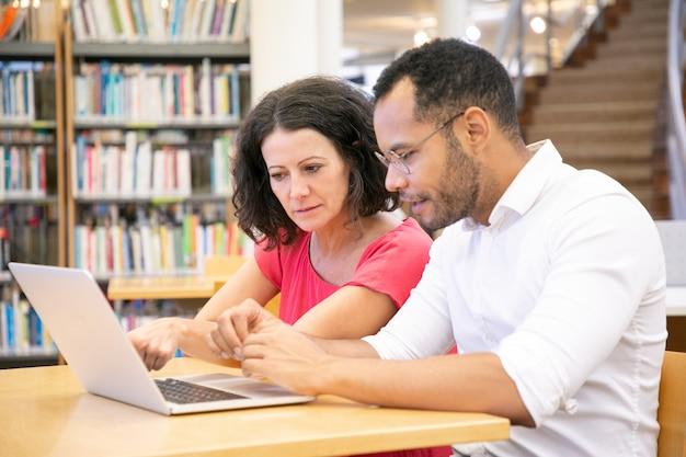 Pareja de estudiantes universitarios adultos que miran contenido en la computadora