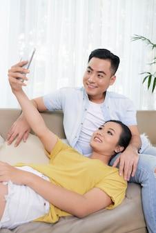 Pareja étnica moderna tomando selfie en sofá