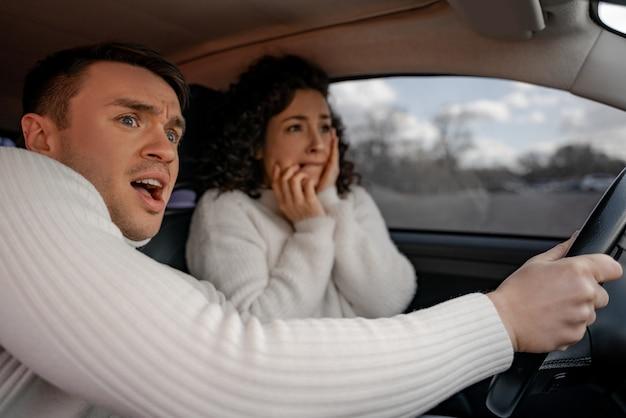 Pareja europea asustada en automóvil personal en accidente. hermosa chica rizada y hombre adulto se sorprende. el hombre agarra el volante de la mujer. concepto de conducción de automóviles
