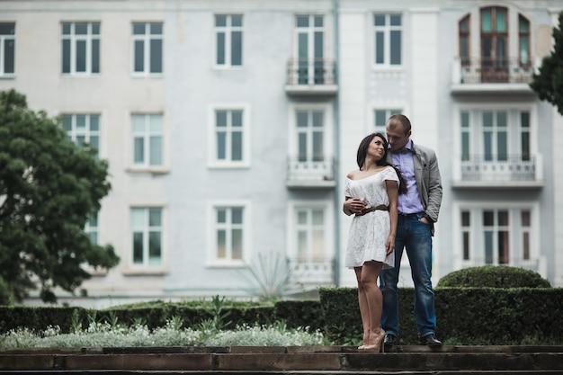 Pareja europea joven y hermosa pasando un buen rato en el fondo de la ciudad
