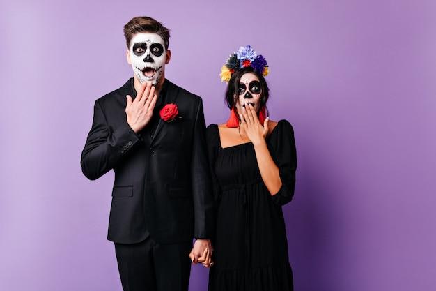 Pareja europea sorprendida con maquillaje espeluznante cogidos de la mano sobre fondo púrpura. jóvenes en ropa negra posando en traje de zombie en halloween.