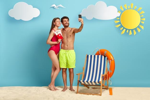 Pareja europea se toma selfie en teléfono celular, posa en la playa con pasaporte y boletos aéreos