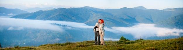 Pareja de excursionistas cubiertos con una manta de pie juntos en una colina