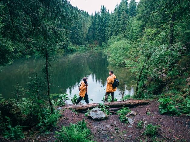 Pareja de excursionistas en impermeable amarillo mirando mochileros de lago de montaña
