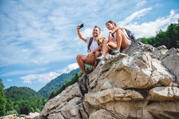 Pareja de excursionistas con perro en la cima de la montaña tomando foto