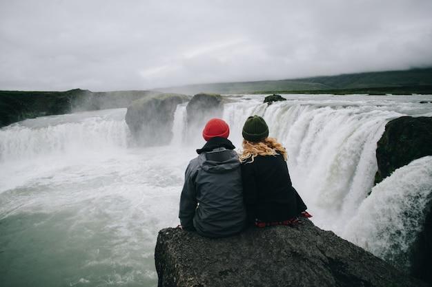 Pareja de excursionistas sentarse sobre el acantilado de la cascada