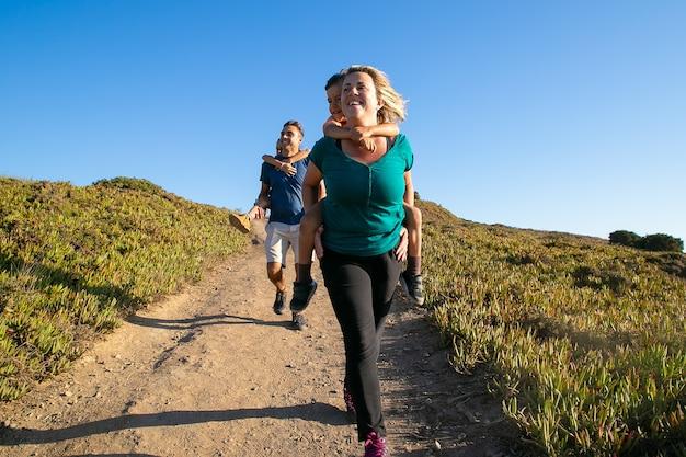 Pareja de familia alegre y niños disfrutando de caminatas en el campo, caminando por el sendero. dos niños montados en la espalda y el cuello de los padres. vista frontal. concepto de naturaleza y recreación