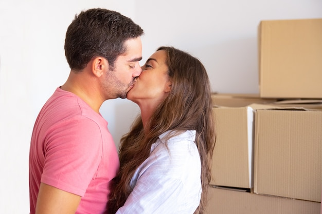 Pareja de familia feliz mudándose a casa nueva, de pie cerca de cajas de cartón y besos