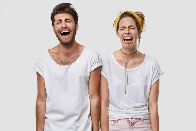 Pareja familiar deprimida llora desesperadamente, siente emociones negativas, usa camiseta blanca informal, frunce el ceño con desesperación, modela sobre la pared, descubre noticias trágicas