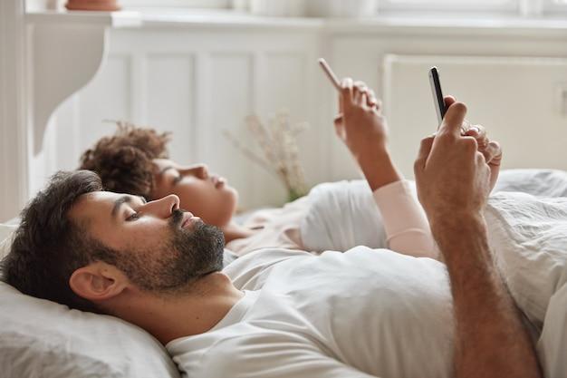 La pareja familiar ignora la conversación animada antes de dormir, usa el teléfono inteligente, mira el video