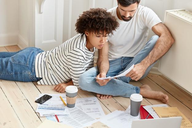 Pareja familiar lleva la contabilidad de la casa, discute planes y pagos futuros