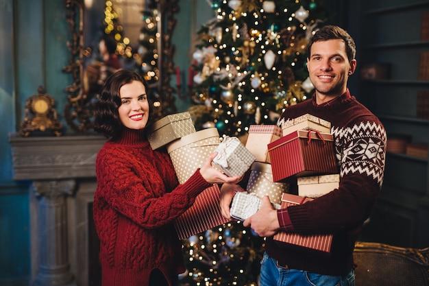 Pareja familiar de pie cerca de año nuevo decorado o árbol de navidad, tiene muchos regalos