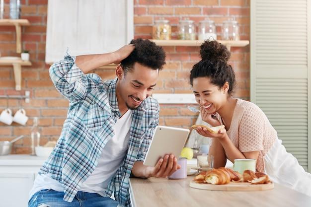 Pareja familiar positiva sonríe ampliamente mientras mira comedia en tableta, use conexión gratuita a internet en casa,