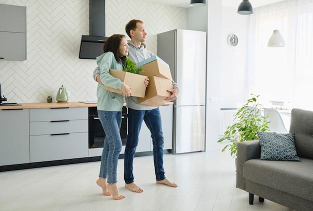 Pareja familiar saliendo de su apartamento, llevando cajas de cartón y muebles. longitud total. concepto de mudanza o reubicación