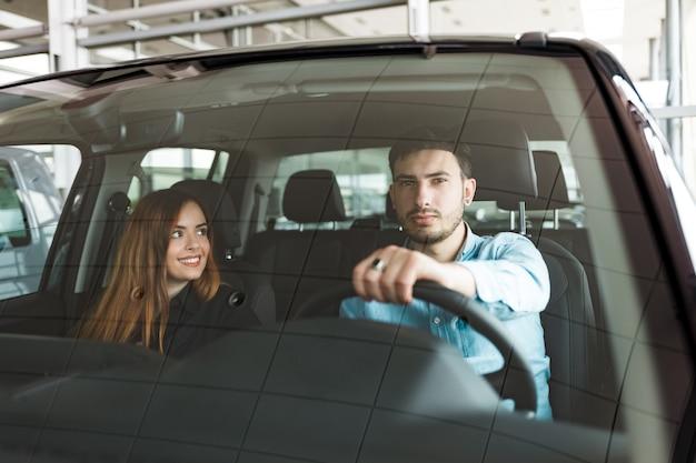 Pareja familiar en su auto nuevo en el concesionario de automóviles