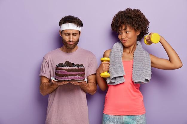 Pareja familiar tiene entrenamiento activo, vestida con ropa deportiva, levanta pesas, se para uno al lado del otro, mira con tentación en el pastel