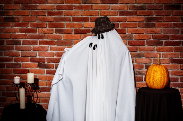 Pareja de fantasmas posando sobre pared de ladrillo