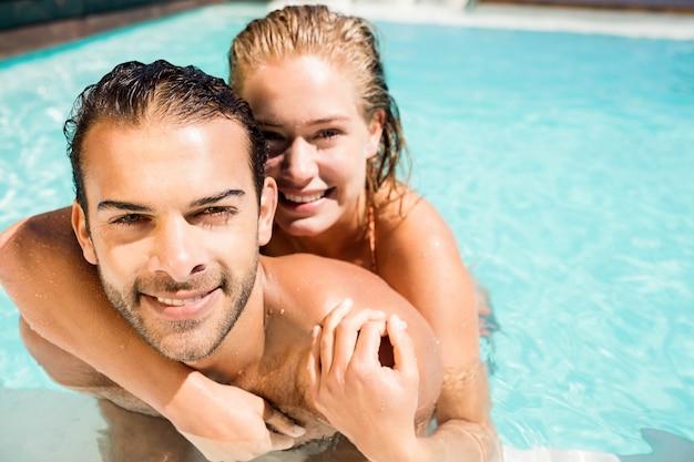 Pareja feliz abrazando en la piscina
