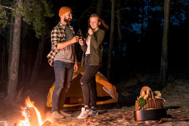 Pareja feliz acampando en la noche