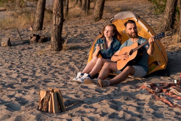 Pareja feliz acampando y tocando la guitarra.
