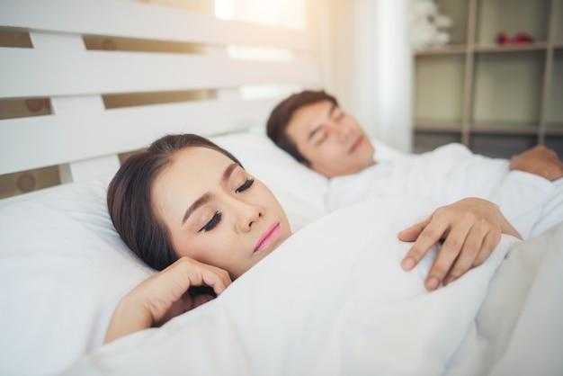 Pareja feliz acostado juntos en la cama