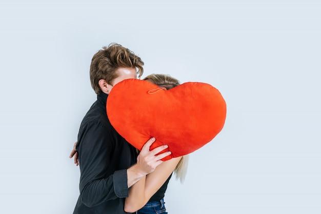Pareja feliz amando juntos sosteniendo un corazón rojo