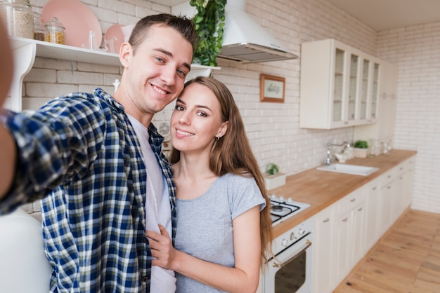 Pareja feliz en el amor haciendo selfie en cocina
