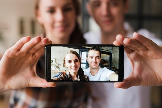 Pareja feliz en el amor haciendo selfie juntos