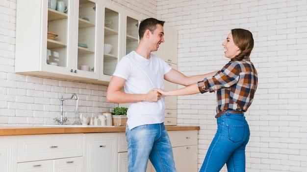 Pareja feliz en el amor jugando en la cocina
