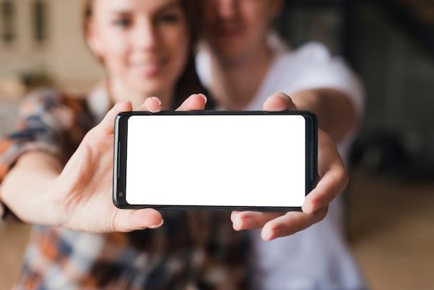 Pareja feliz en el amor que muestra la pantalla del teléfono inteligente