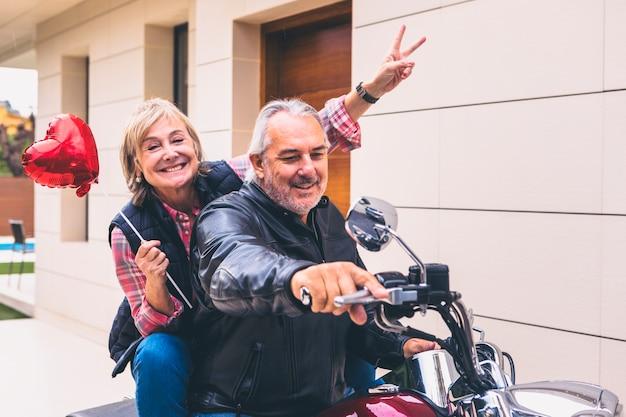 Pareja feliz anciana montando motocicleta