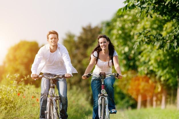 Pareja feliz andar en bicicleta a lo largo de un camino soleado